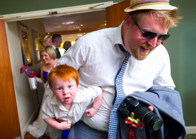 wedding-guest-carrying-boy-under-arm