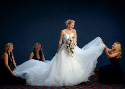 bridesmaids-adjusting-brides-dress
