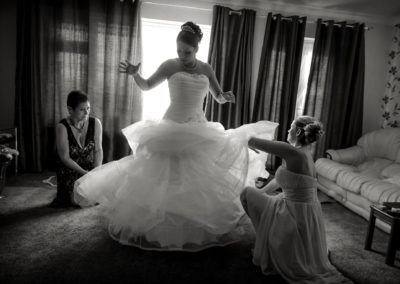 bridesmaids-helping-bride-with-dress