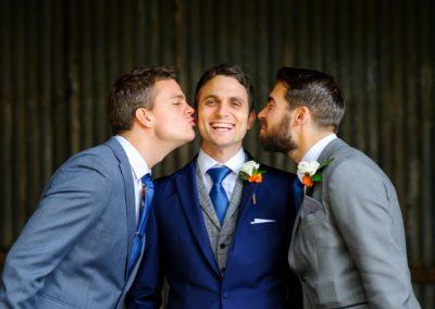 ushers-kissing-groom